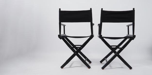 Parte de trás da cadeira preta de dois diretores, usada na produção de filmes, indústria cinematográfica em fundo branco