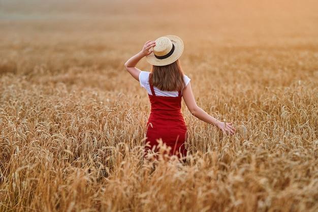 Parte de trás da mulher jovem e serena, calma e livre, usando chapéu de palha e jeans vermelho, em pé no campo de trigo seco amarelo dourado e desfrutando de um belo momento de liberdade