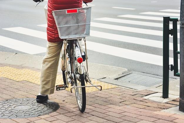 Parte de trás da mulher na bicicleta vintage esperando na calçada