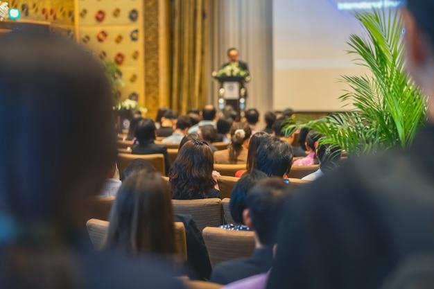 Parte de trás do público ouvindo o orador com pódio no palco na sala de conferências