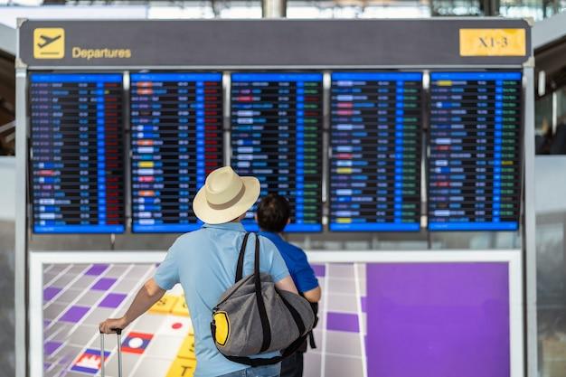 Parte de trás do viajante com a bagagem em pé sobre a placa de voo para check-in