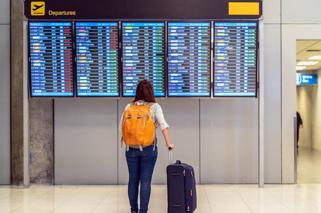 Parte de trás do viajante com a bagagem em pé sobre a placa de voo para o check-in