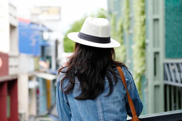 Parte de trás do viajante de mulher em pé com o fundo da cidade ao ar livre, estilo de vida casual