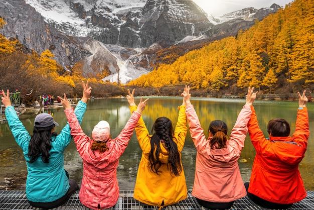 Parte de trás dos viajantes asiáticos woemn olhando e passeando sobre o lago pérola com montanha de neve