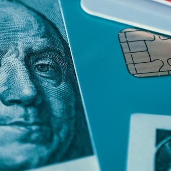 Parte de um cartão de crédito e uma nota de cem dólares