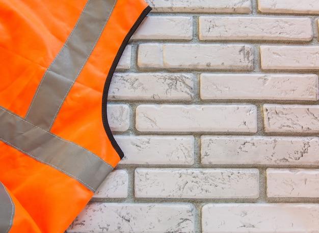 Parte de um colete de proteção laranja contra um fundo branco de tijolos, um colete de segurança de emergência com uma cópia do espaço