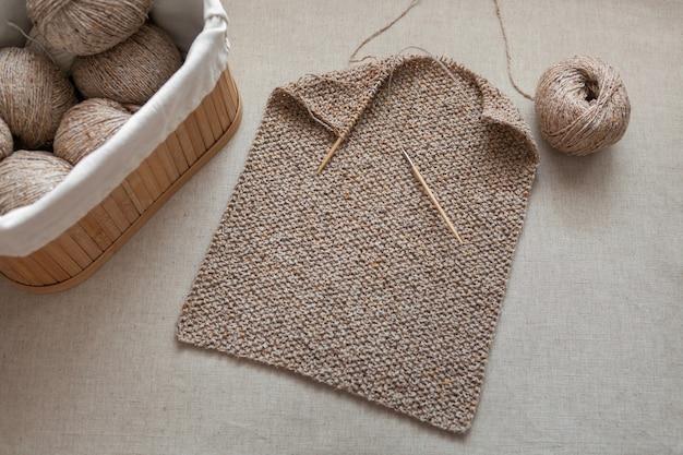 Parte de um lenço tricotado com agulhas circulares de bambu, bolas de fios de lã em uma cesta com foco seletivo