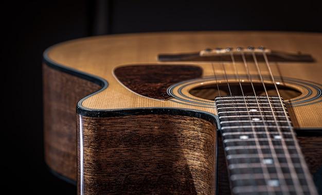 Parte de um violão, braço da guitarra com cordas em um fundo preto.