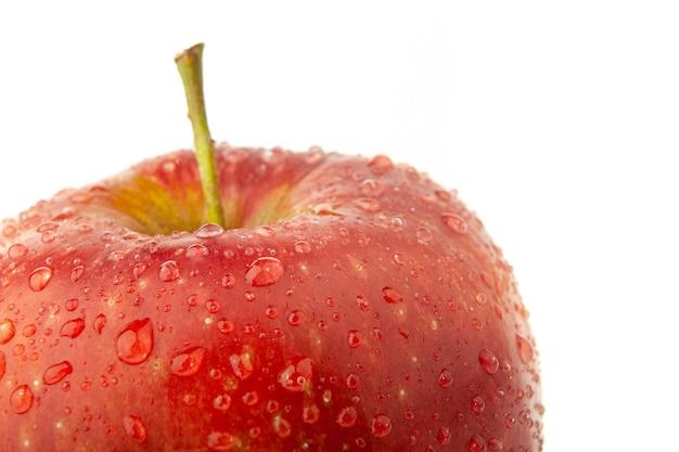 Parte de uma maçã vermelha com gotas de água no branco