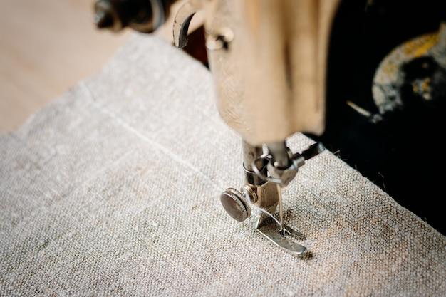 Parte de uma máquina de costura vintage e item de vestuário. agulha de aço com looper e close-up do calcador.