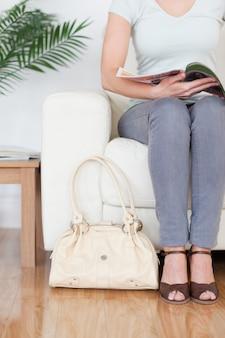 Parte de uma mulher em um sofá com uma bolsa e uma revista