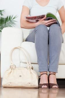 Parte de uma mulher fofa em um sofá com uma bolsa e uma revista