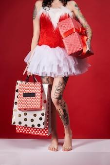 Parte de uma mulher segurando uma sacola de compras e um presente de natal