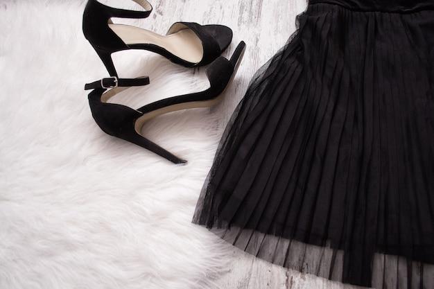 Parte de uma saia plissada preta e sapatos pretos.