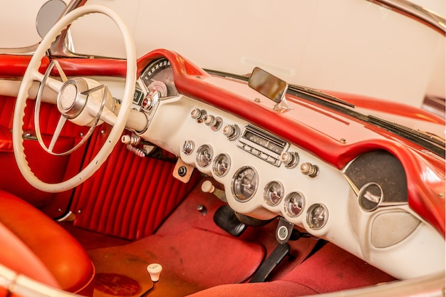 Parte dianteira do interior vermelho de um carro, incluindo o volante branco