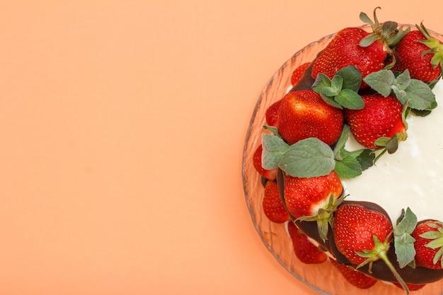 Parte do bolo de chocolate caseiro decorado com morangos frescos na placa de vidro e em fundo de cor laranja. vista superior com espaço de cópia