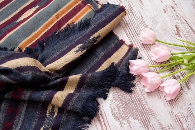 Parte do cachecol em listras e ornamento, tulipas cor de rosa