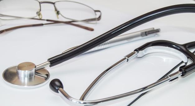 Parte do close-up do estetoscópio no local de trabalho de um médico de família, é realizado um exame médico, o conceito de assistência médica.
