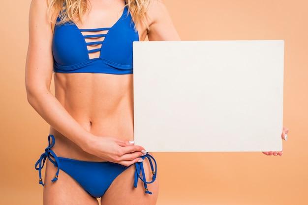 Parte do corpo da jovem mulher em traje de banho azul com papel em branco