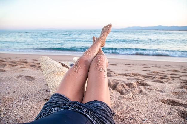 Parte do corpo. pés femininos na areia na praia à beira-mar.