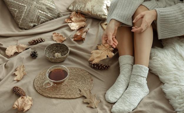 Parte do corpo, uma mulher em uma cama aconchegante com uma xícara de chá entre as folhas de outono.