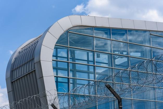 Parte do edifício moderno do aeroporto atrás do arame farpado.