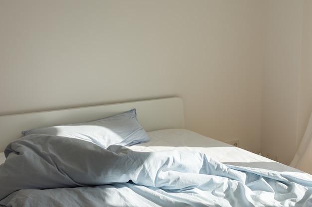 Parte do interior da casa ou do hotel, cama após dormir de manhã ao sol, cama branca com colchão e lençóis azuis