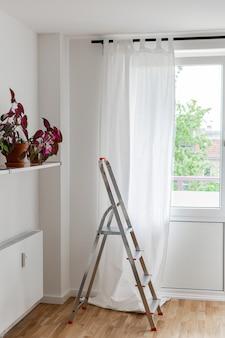 Parte do interior da casa ou do hotel, escada de ferro contra a parede de uma janela com cortinas brancas e uma prateleira com flores e radiador