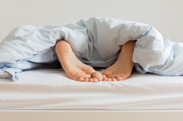 Parte do interior da casa ou do hotel, pernas masculinas aparecem debaixo das cobertas, homem dormindo em uma cama branca com lençóis azuis pela manhã