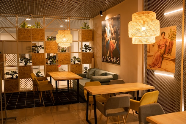 Parte do interior de um café moderno e aconchegante com mesas de madeira, poltronas, plantas domésticas e pôsteres nas paredes