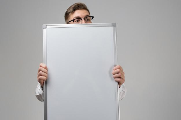Parte do jovem de óculos com placa magnética limpa nas mãos isolado branco
