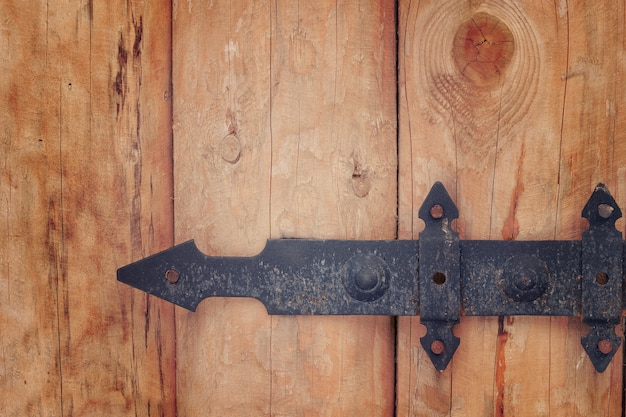 Parte do portão de madeira com dobradiças forjadas