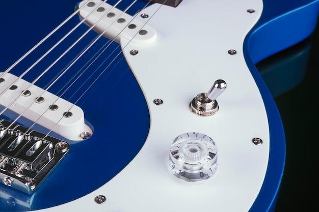 Parte frontal do corpo de uma guitarra elétrica em fundo preto.