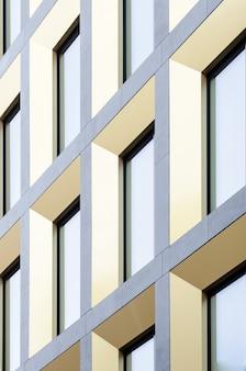 Parte geométrica da fachada do edifício. arquitetura moderna de paredes e janelas comerciais de vidro.