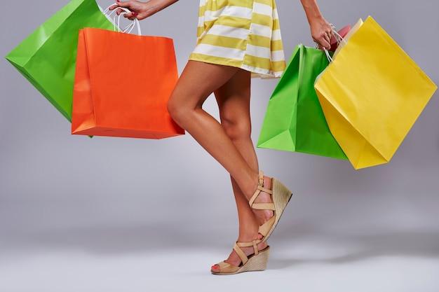 Parte inferior da mulher com sacolas de compras