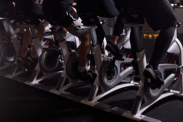 Parte inferior das bicicletas ergométricas em uma academia de ginástica, pessoas andando de bicicleta, malhando, treinando