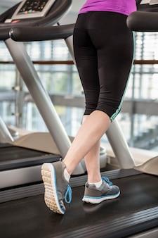 Parte inferior, de, ajuste, mulher, ligado, treadmill, em, a, ginásio