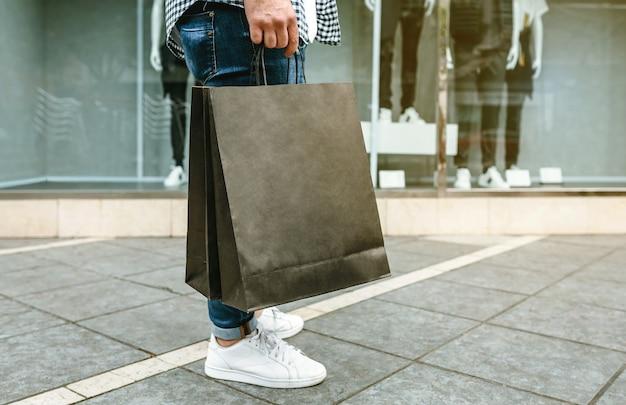 Parte inferior de um jovem irreconhecível fazendo compras com sacos de papel nas mãos