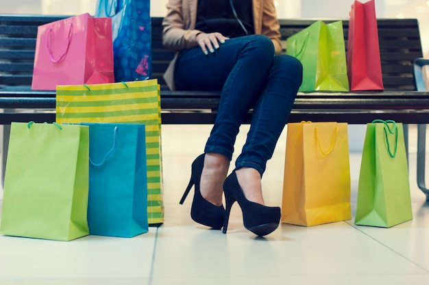Parte inferior de uma jovem com sacolas de compras no shopping