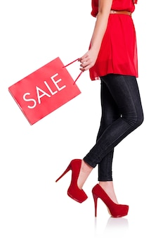 Parte inferior de uma mulher com sua sacola de compras vermelha