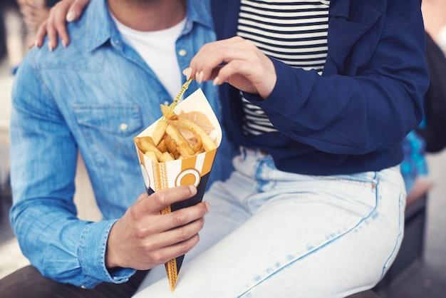 Parte inferior do casal comendo batatas preparadas