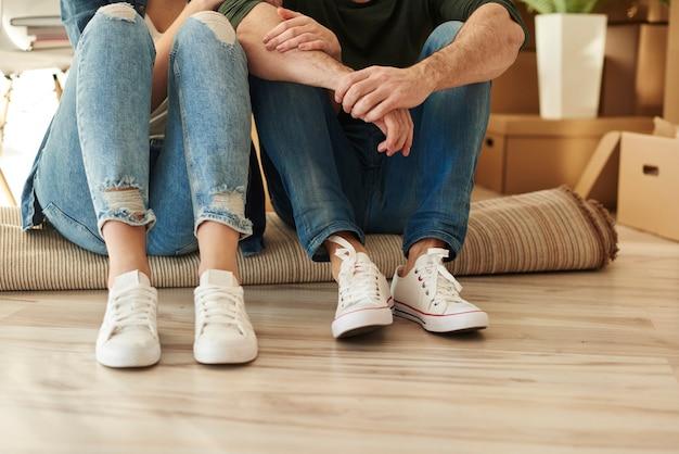 Parte inferior do casal sentado no tapete