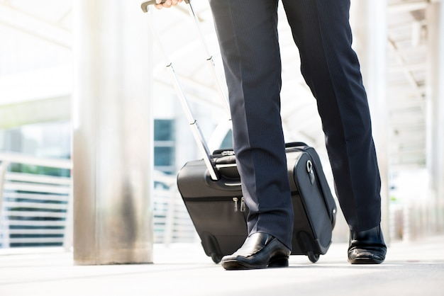 Parte inferior do empresário viajando andando e puxando a bagagem