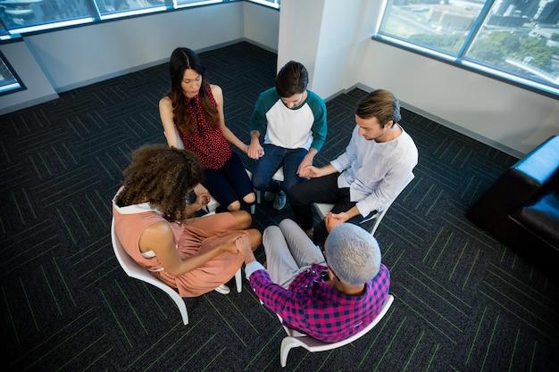 Parte intermediária da equipe de negócios criativos segurando as mãos uns dos outros no escritório