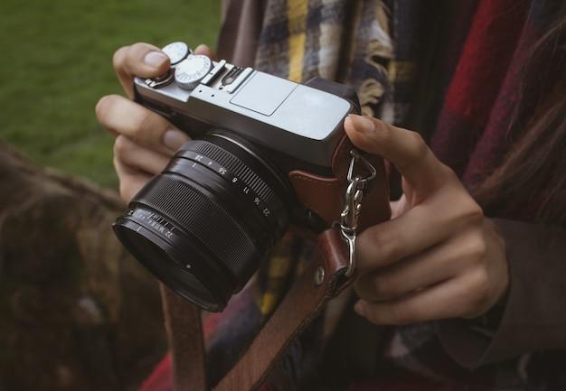 Parte intermediária da mulher segurando uma câmera digital