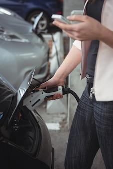 Parte intermediária da mulher usando telefone celular enquanto carrega o carro elétrico
