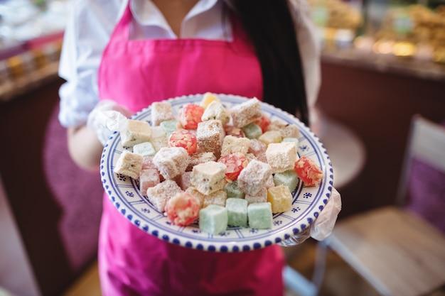 Parte intermediária de uma lojista segurando uma bandeja de doces turcos no balcão