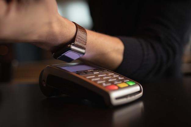 Parte intermediária do homem fazendo pagamentos por meio de smartwatch