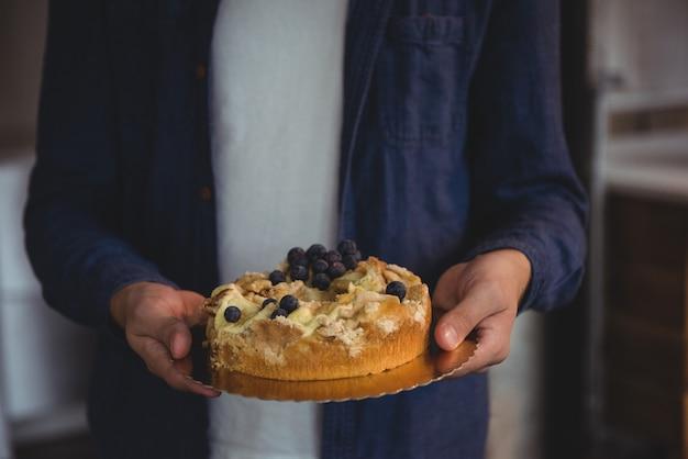 Parte intermediária do homem segurando bolo de mirtilo na sala de estar