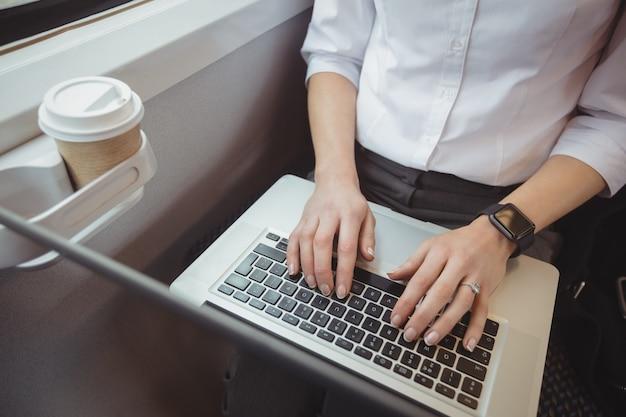 Parte média da mulher usando laptop